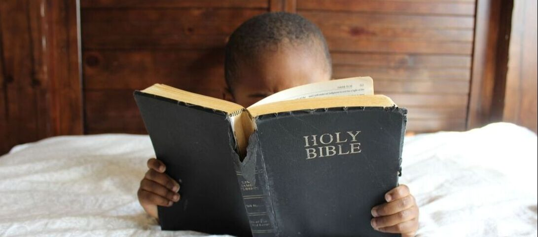 Young boy reading bible.